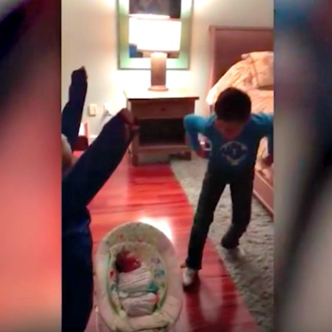 screenshot from video of baby in bed room and boys excited