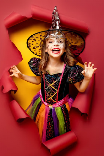 A girl dressed as a rainbow witch with a silver galaxy hat is bursting through a wall