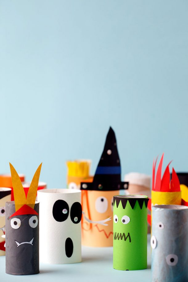 A collection of Halloween toilet paper roll crafts ready to play with on a blue background.