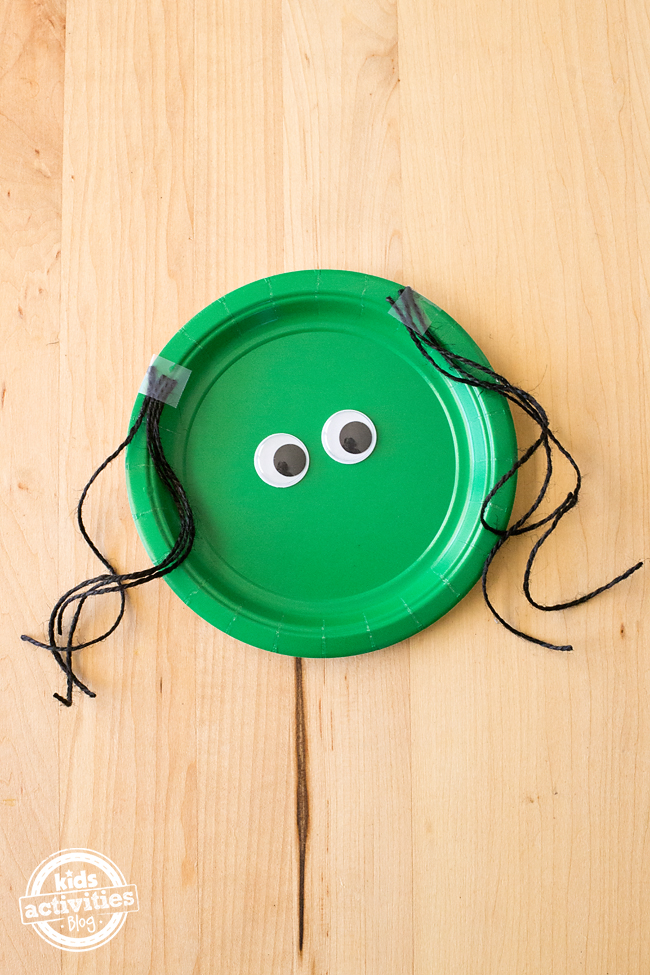 Step 2 to Make Paper Plate Withes - add googly eyes to green paper plate and 8 strands of string for witch's hair