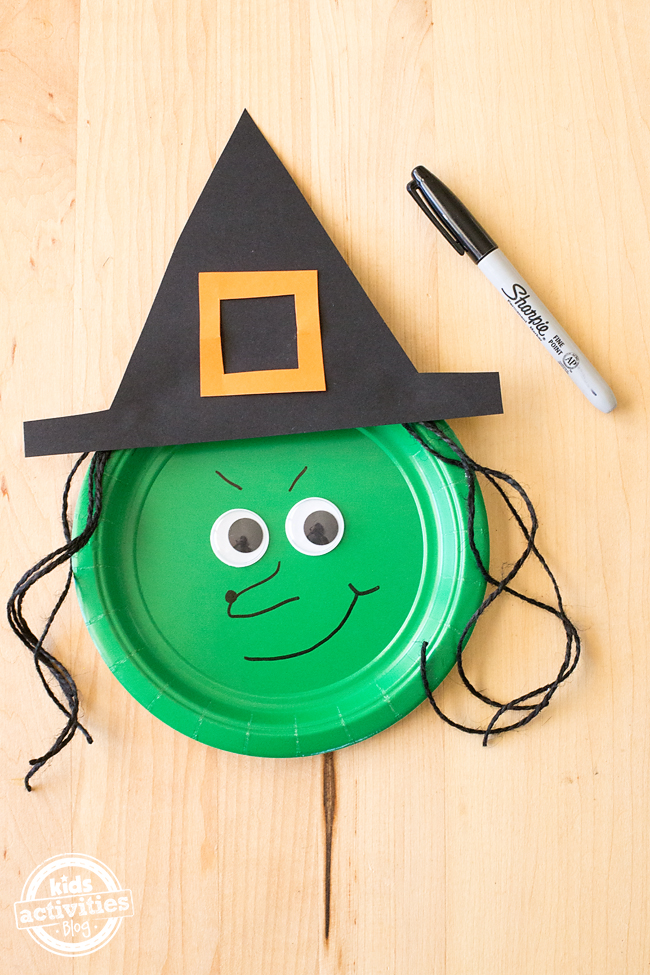 Step 3 How to Make a Paper Plate Witch - Add the witches hat which is made of black construction paper and a yellow construction paper buckle.