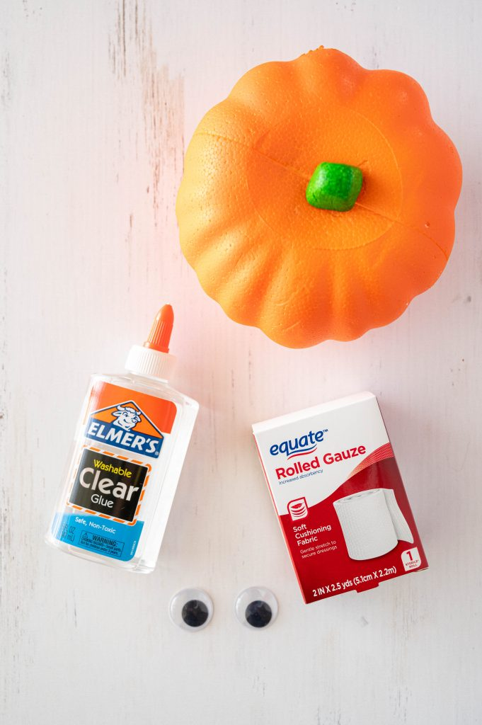no-carve mummy pumpkin supplies on a white wood table