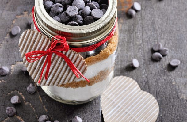 cookie ingredients layered in a mason jar with a twine tie and hearts
