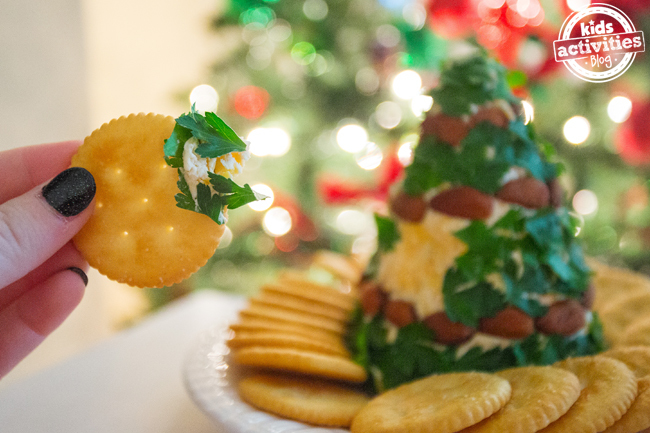 Cheese Christmas tree with a hand dipping a cracker into it.