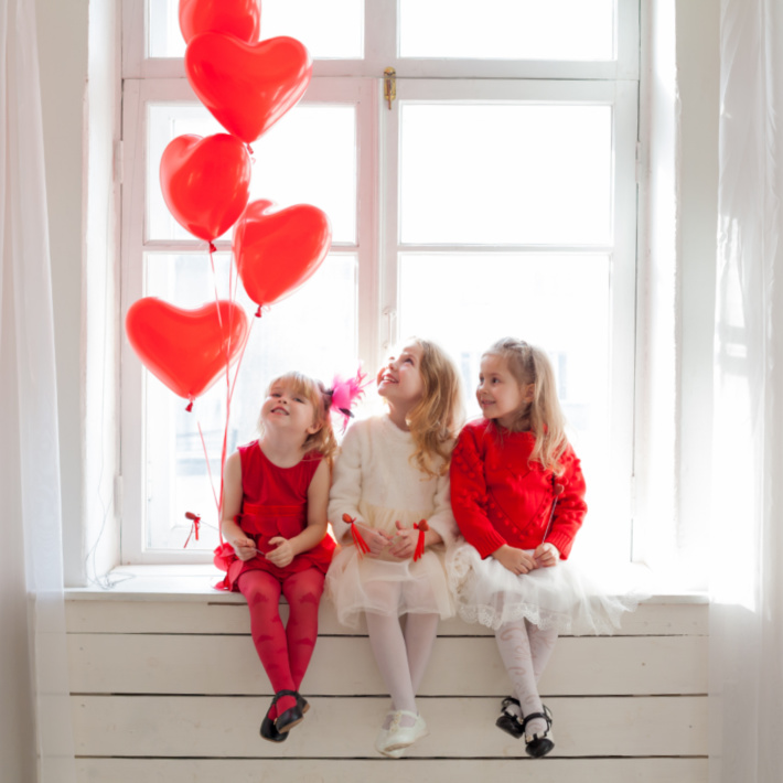 Photoshoot ideas for Valentines Day with Kids - three girls and red heart balloons