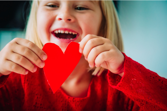 Valentine photo shoot with kids - casual shot with girl holding homemade paper heart
