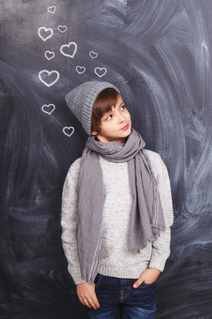 Valentine photoshoot ideas with kids - boy on chalkboard with heart thought bubbles