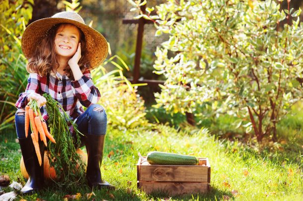 Food coloring alternatives using carrots that the girl is holding while sitting on a pumpkin in her farming clothes outside on a sunny day.