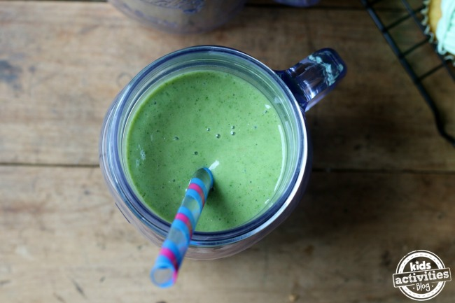 Earth day food ideas like this green smoothie that looks thick and yummy in a mason jar with a pink and blue straw in it.