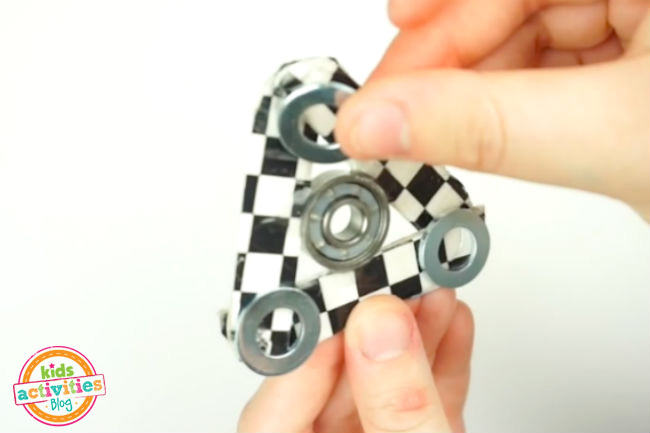 Add Weight to Fidget Spinner craft - washers glued to each corner with fingers placing them properly