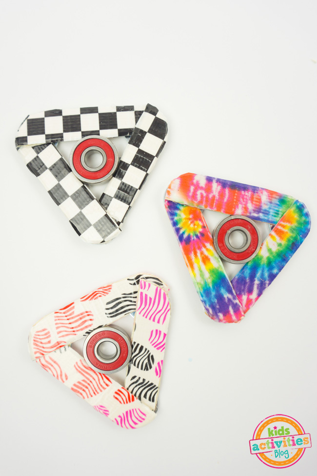 How to Make Fidget Spinner craft - three completed homemade fidget spinners shown - one with checker board tape, one decorated with rainbow tie dye tape and one with multi-color hearts