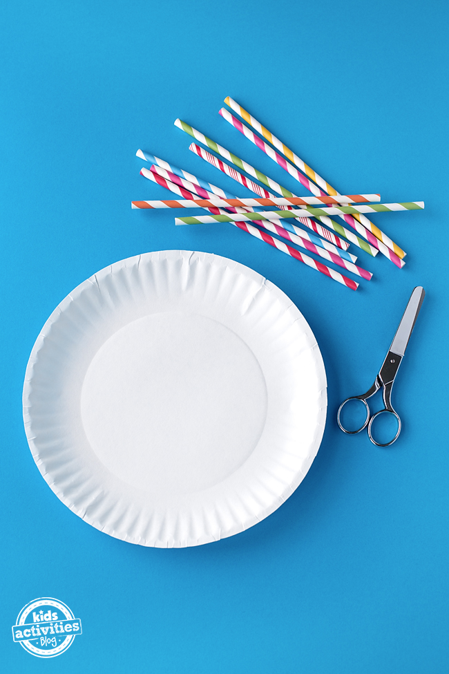 A paper plate, a pair of scissors, and some straws sit out on a blue background, ready to make a marble maze.