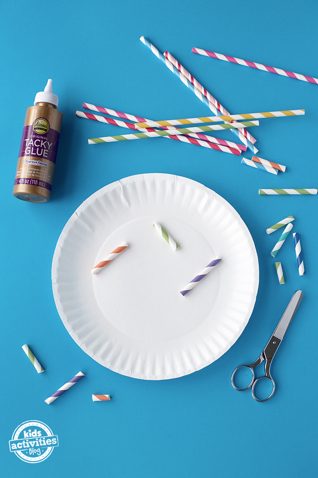 The scissors have been used to cut the straws into pieces. Tacky glue is now being used to attach the pieces of straw to the paper plate.