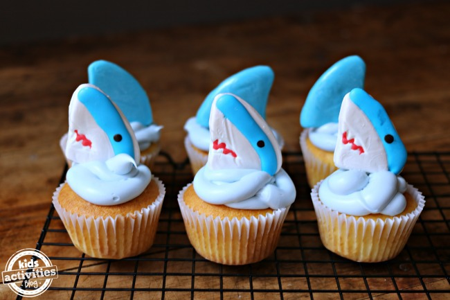 Shark cupcakes with blue frosting that looks like water and gummy shark decorations