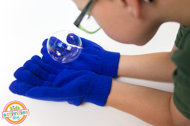 Catching a Bubble made from homemade bubble solution on a gloved hand - Kids Activities Blog