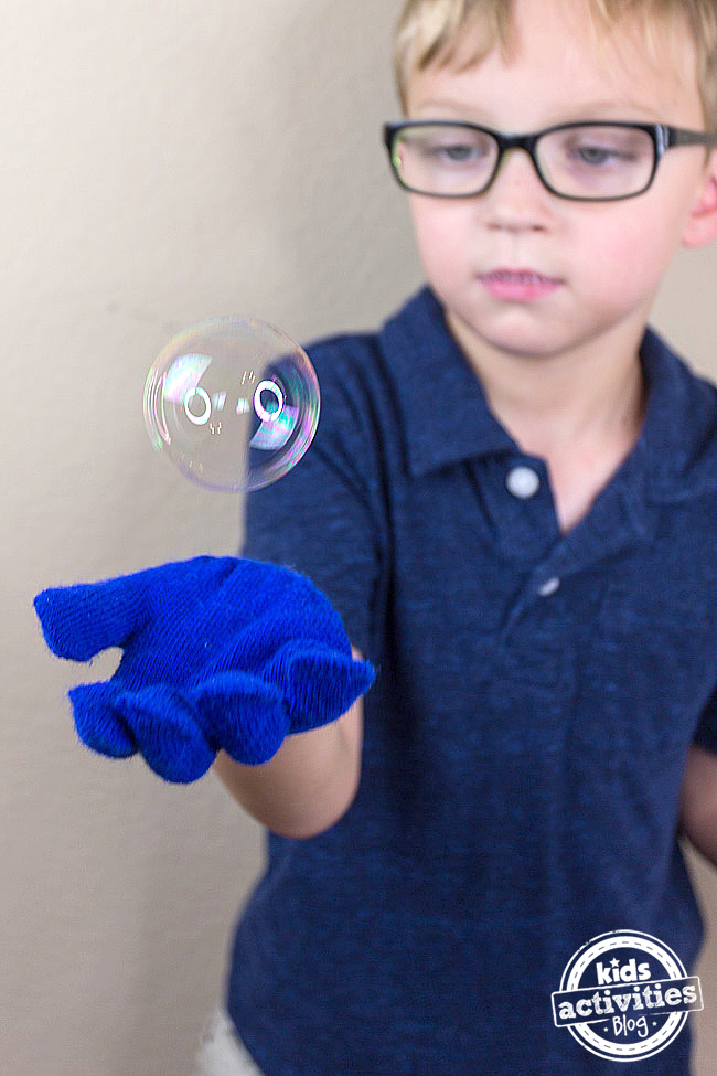 Bouncing Bubbles - homemade bubble solution bubble in the air over a winter gloved hand of boy bouncing the bubble