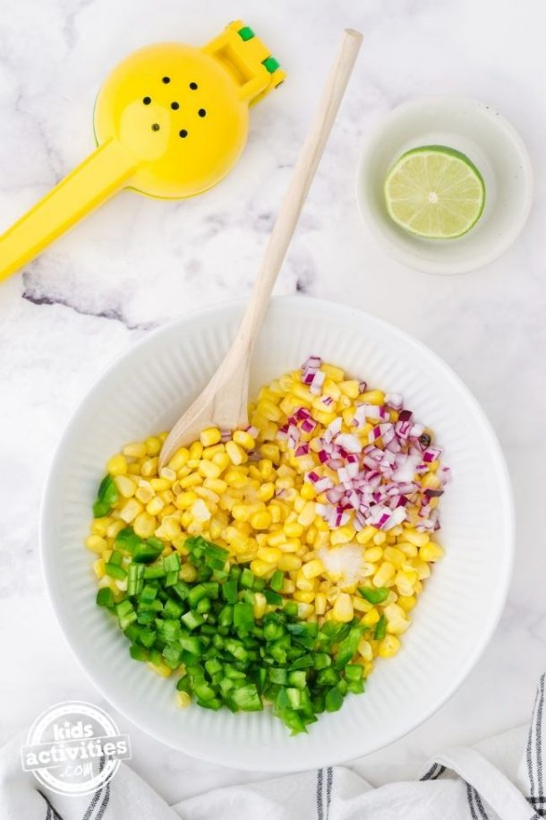 Ingredients for corn salsa in a large white bowl with a wooden spoon in it ready to stir.