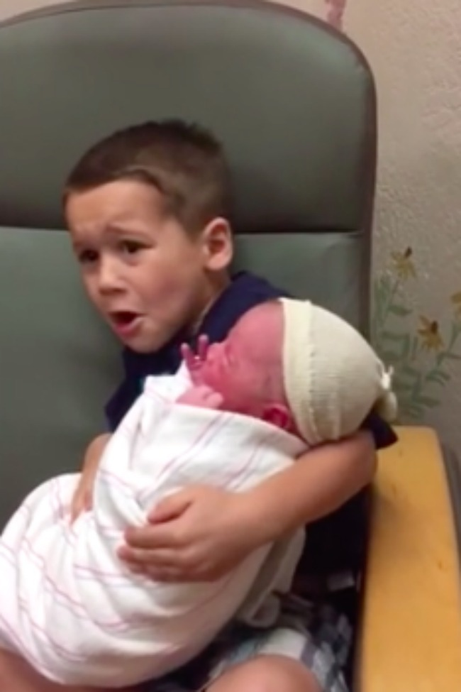 Brother Has Funny Reaction To Holding New Baby [Video]