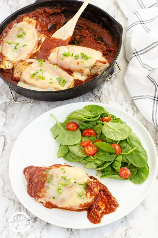 Chicken Parmesan on a plate with a spinach salad beside it.