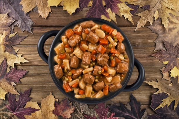A large bowl of meaty chili sits on a wooden table, surrounded by fall leaves.