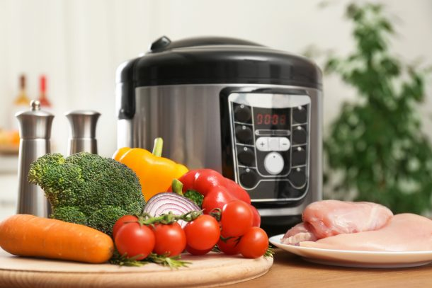 An instant pot sits behind two piles of food. One is vegetables, the other is meat.