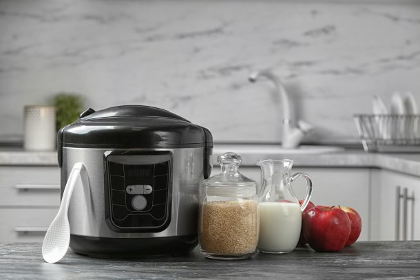 An instant pot sits on a counter with a plastic spoon, containers of rice and milk, and some apples.