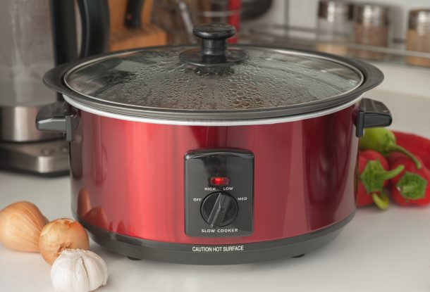 A crock pot sits on a countertop. To the sides are onions, garlic, and peppers.