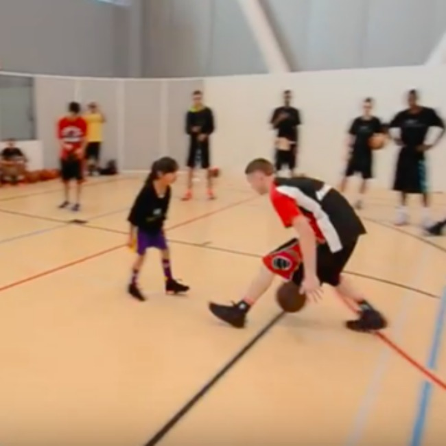 screenshot from video of professor and girl practicing basketball on a court