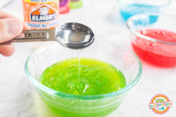 A spoon of elmers magical liquid is poured into a bowl of green glitter glue to make colored slime