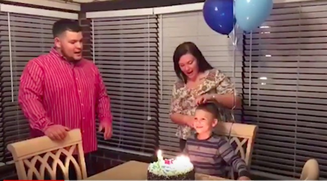 screenshot of video of boy blowing out his birthday candles