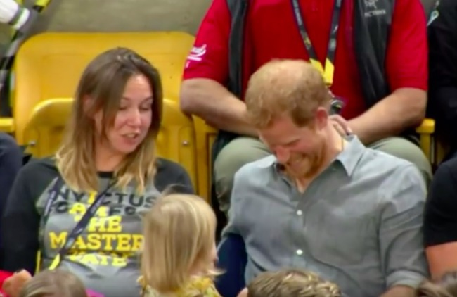 screenshot of little girl stealing Prince Harry's popcorn and he is laughing