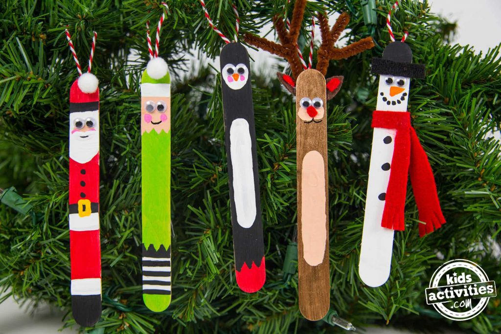 Popsicle stick Christmas ornaments that look like: Santa, and elf in green, a penguin, Rudolph, Frosty