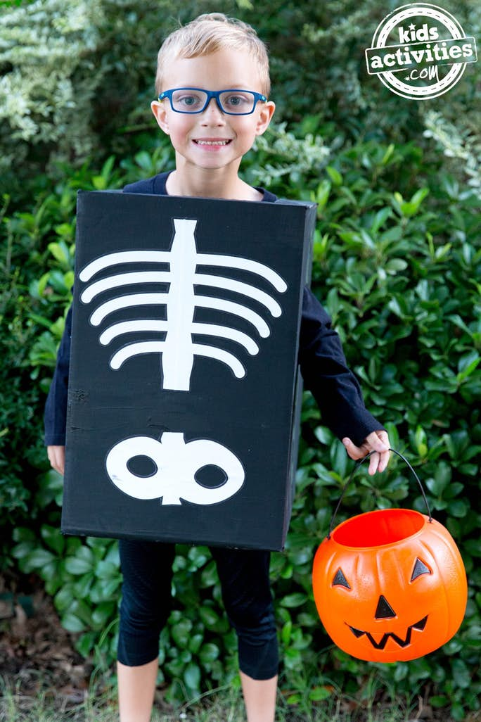 kids skeleton costume that is a black painted box with white painted spine, ribs, and pelvis.