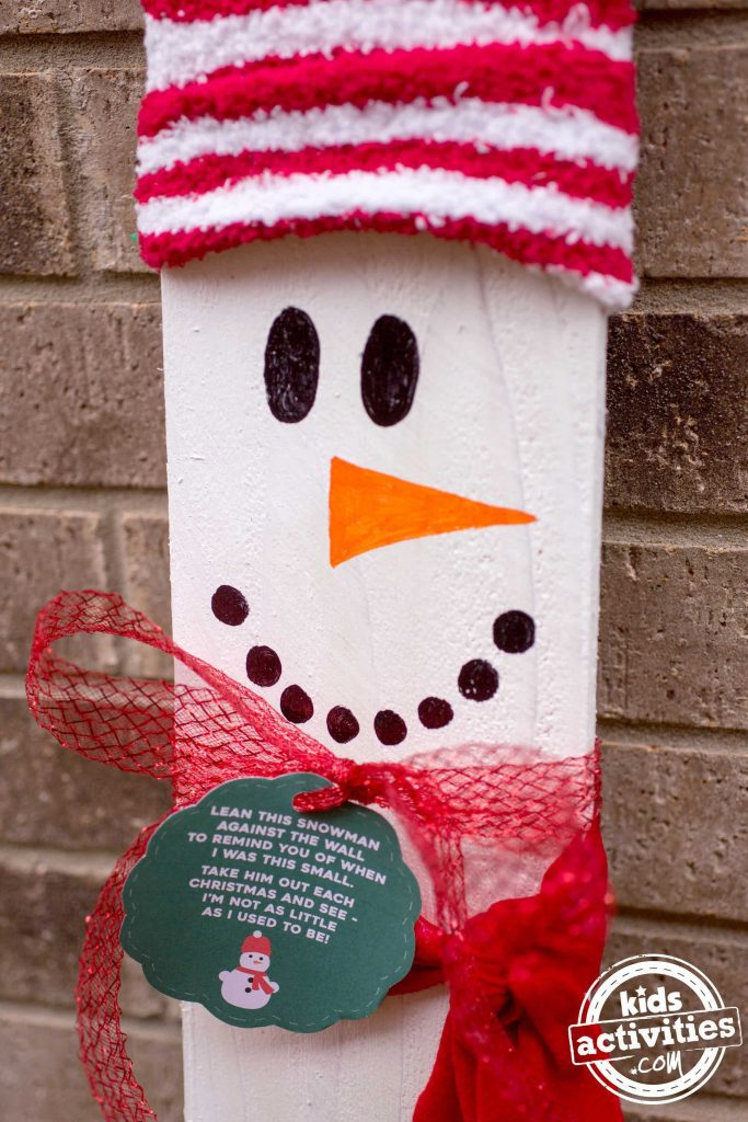 Snowman made out of wood with a hat, mouth, eyes, nose, a ribbon scarf, and green gift tag and poem.