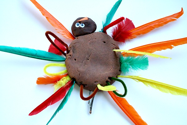 Playdough turkey with feathers and pipe cleaners