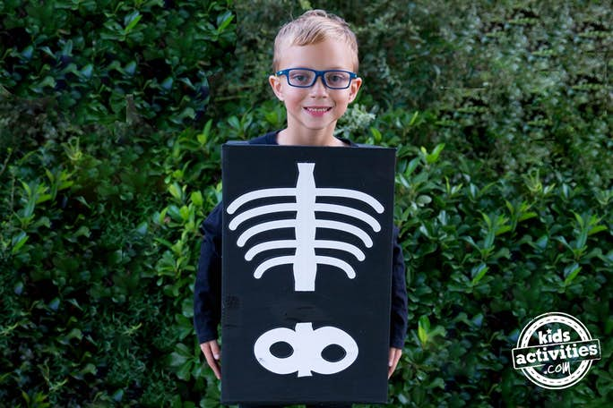 This Kids Skeleton Costume is so cute and easy, the child is standing in black clothing, and a black box with white spines, ribs, and pelvis on it.