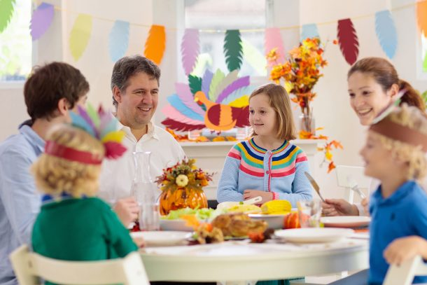 75+ Thanksgiving Crafts & Activities: A picture of a family enjoying crafts and dinner on Thanksgiving Day!