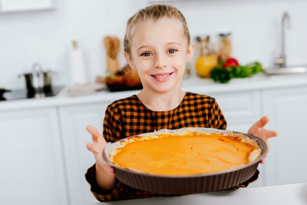 75+ Thanksgiving Crafts & Activities- A kid with a yummy Thanksgiving pumpkin pie.