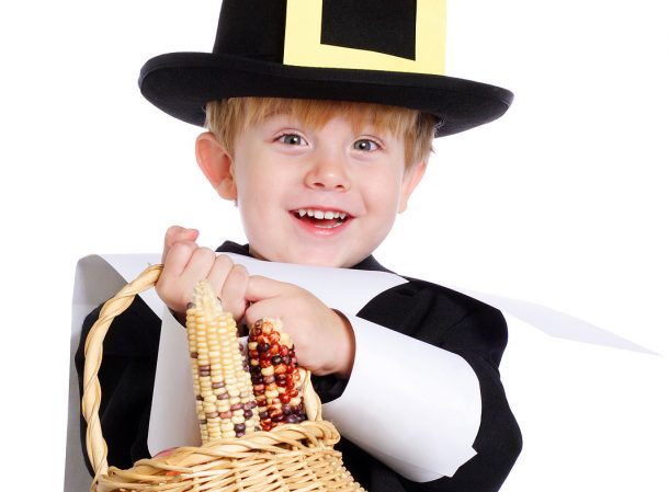 75+ Thanksgiving Crafts & Activities- A picture of a boy with Indian corn.