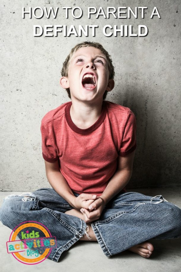How to parent a defiant child - defiant child shown screaming and sitting cross legged on floor