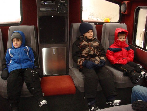 3 boys riding in the snowcat