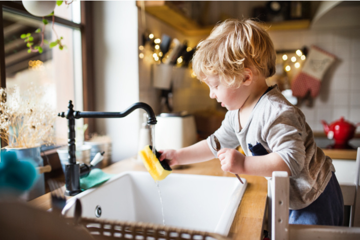 Giant age appropriate chores for kids guide - Kids activities Blog - toddler washing dishes from stool