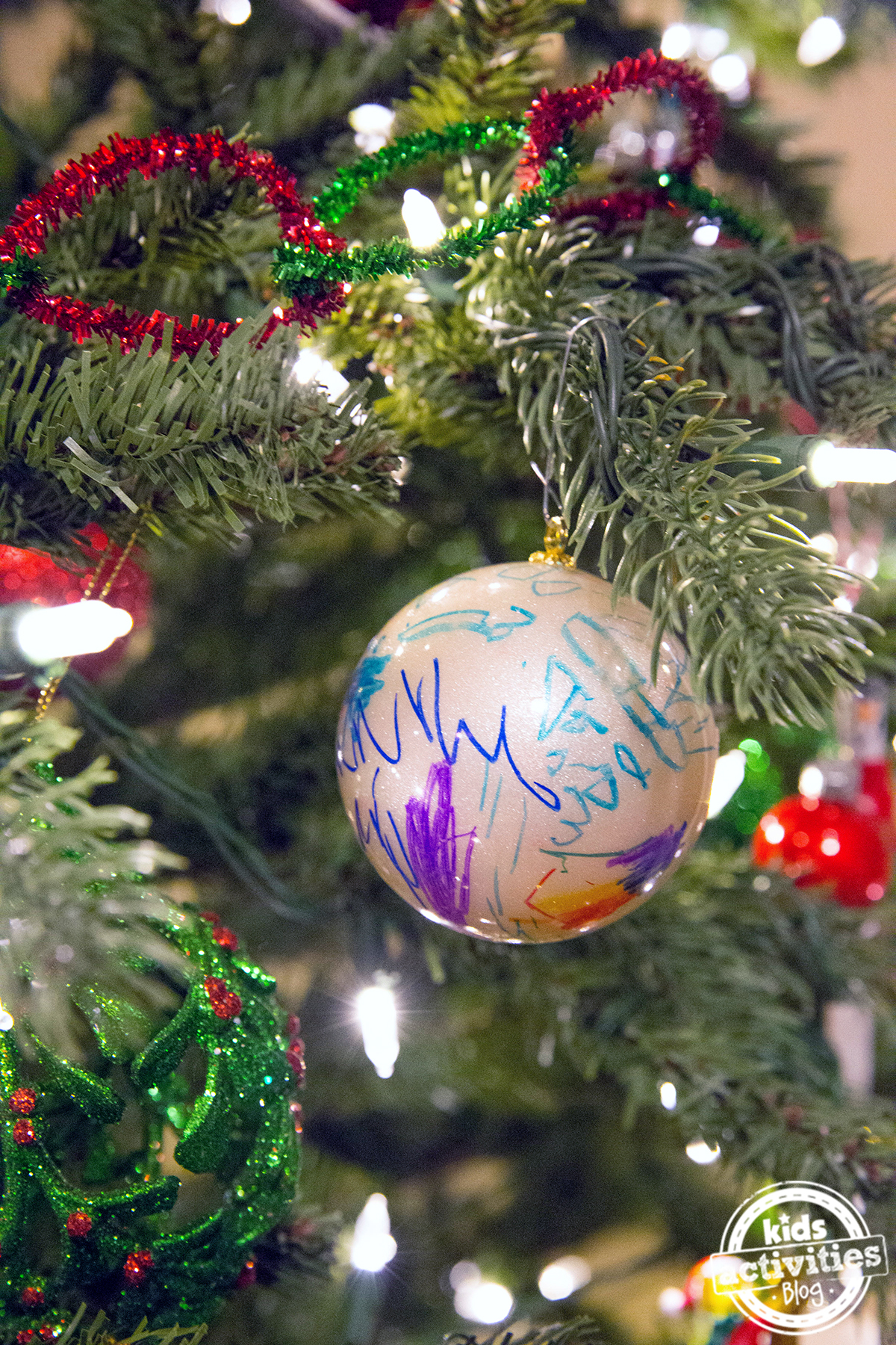 I love this Christmas ornament art where kids have colored on plain white ornaments with blue, purple, and orange markers.