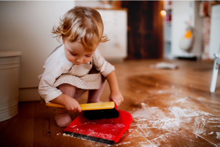 Younger child - toddler using dustpan for chores - Kids Activities Blog