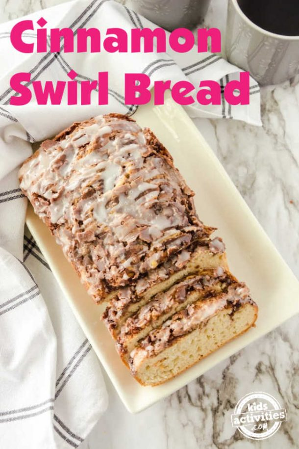 Cinnamon Swirl Bread sliced on a white platter sitting on a marble countertop.
