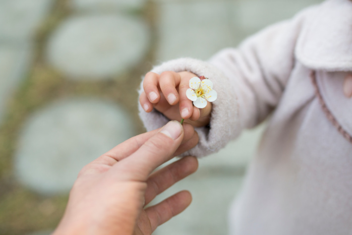 Fine motor control - child holding a flower in pincher grip - Kids Activities Blog