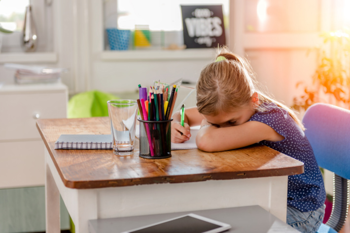 Girl tired writing at desk at home - Kids Activities Blog