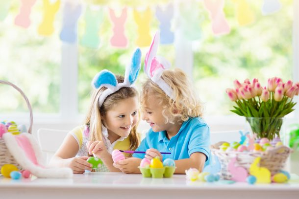 2 girls with bunny ears enjoying their Easter treats which are cupcakes
