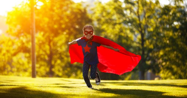 This happy child superhero hero in red cloak at sunset in nature after having their super lunch
