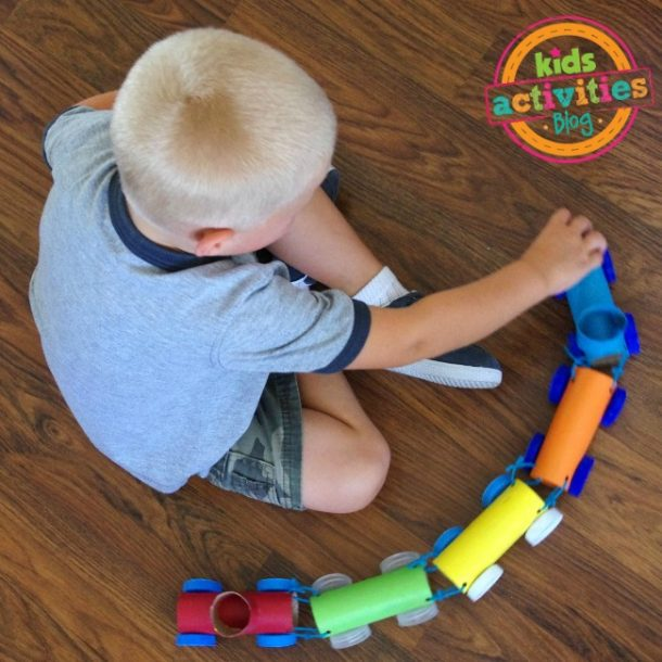 Screen free activities like this toilet paper roll train this little boy is playing with!